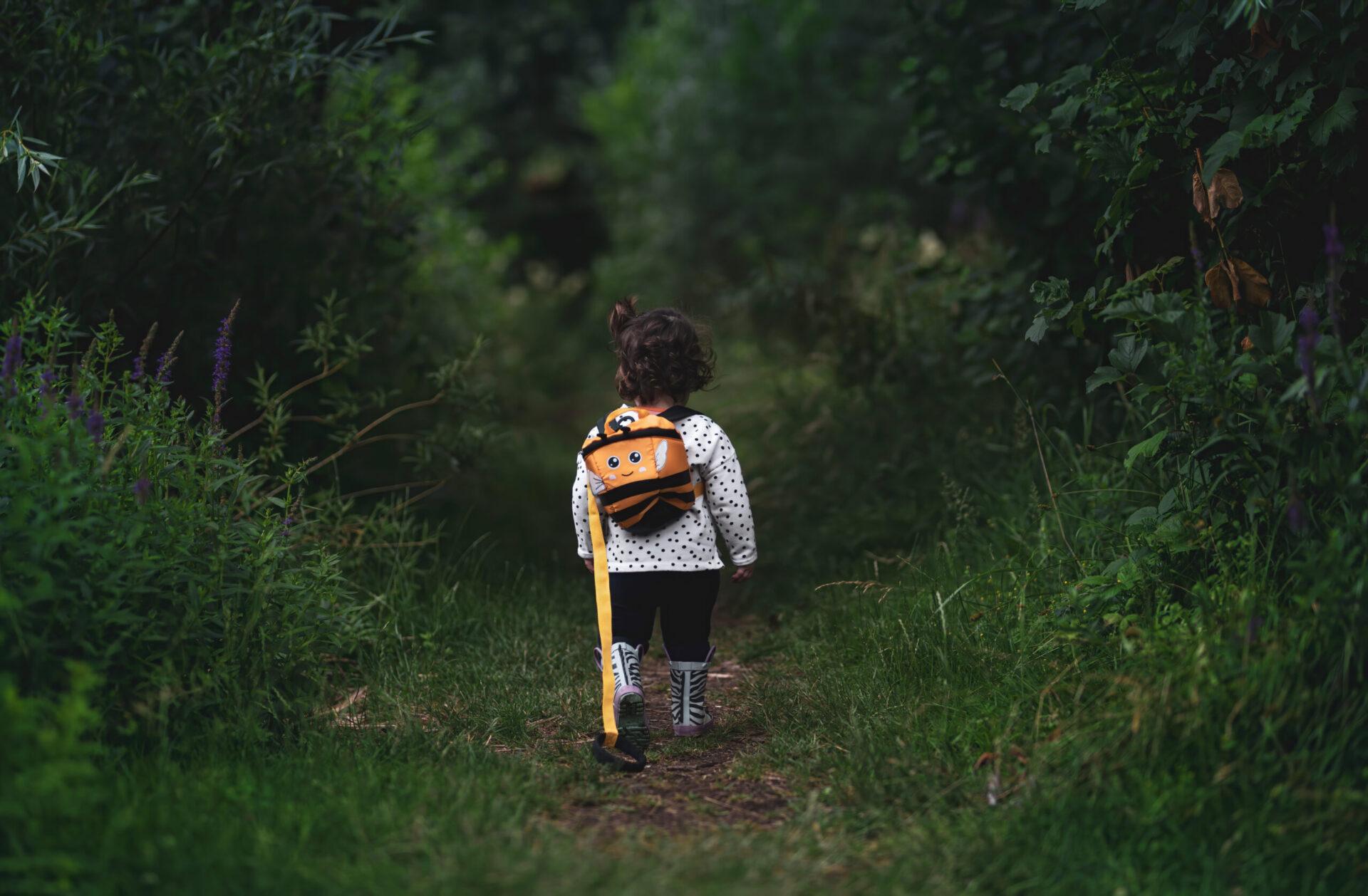 Barn med ryggsäck i en skog som illustrerar alla barns lika rätt.